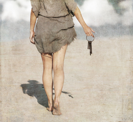 legs open: Woman walking barefoot through the desert with a bundle of keys in her hand, view from back