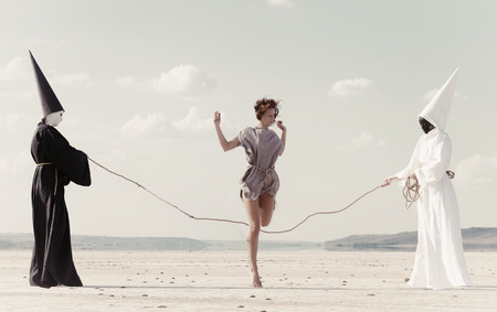 Woman hoping over the rope held by two mysterious persons wearing white and black clothes