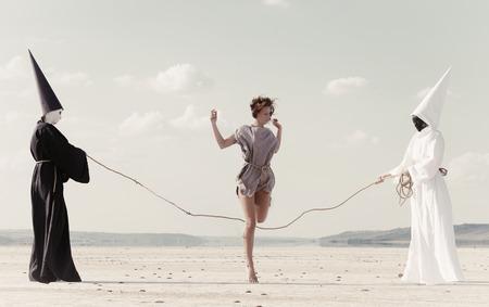 Vrouw in de hoop op het touw gehouden door twee mysterieuze personen, gekleed in witte en zwarte kleding Stockfoto