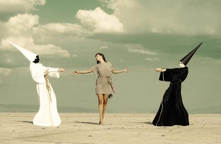 humility: Mujer entre dos personas misteriosas que juegan esfuerzo supremo Foto de archivo