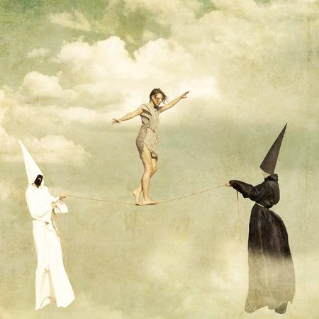 unreal unknown: Donna che cammina lungo una fune tenuta da due misteriosi personaggi che indossano abiti bianchi e neri