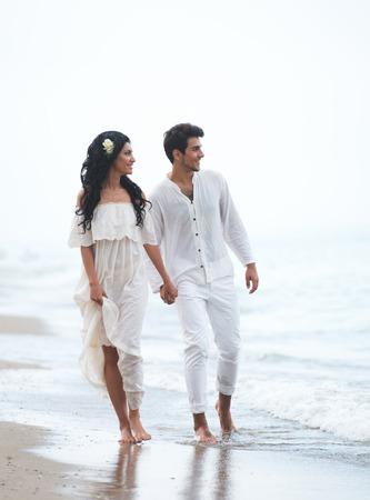 dark haired: Romantic couple walking along the seaside