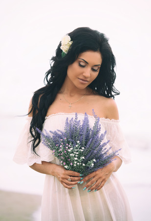 dark haired: Portrait of a beautiful woman with flowers in her hands walking along the beach