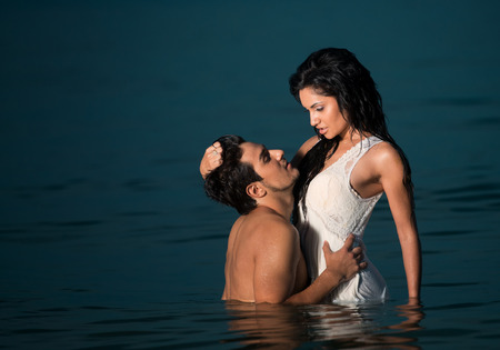 Passionate young couple in water photo