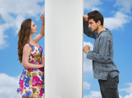 Conflict between man and woman standing on either side of a wall Stock Photo