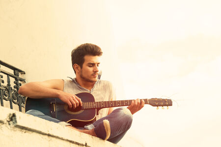 parapet: Portrait of a young guitarist sitting on parapet, view from below