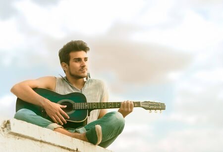 play popular: Portrait of a young guitarist sitting on parapet, view from below