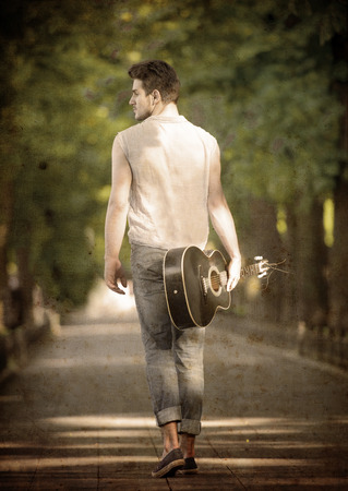 Young guitarist walking away along the boulevard, view from back photo