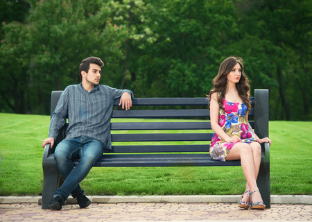 離れて公園のベンチに座っている若いカップル 写真素材