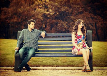dattes: Jeune couple assis dehors sur le banc dans le parc Banque d'images