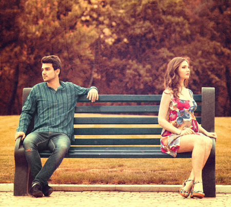 severance: Young couple sitting apart on the bench in the park