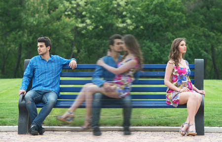 banc de parc: Jeune couple assis dehors sur le banc dans le parc et se souvenir de leur histoire d'amour Banque d'images