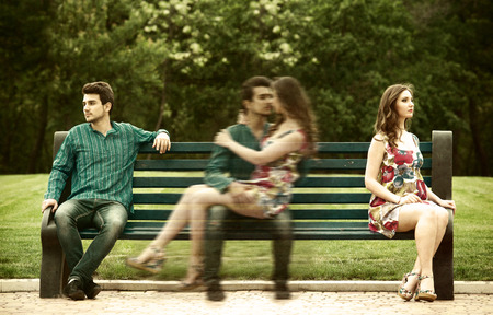Young couple sitting apart on the bench in the park and remembering their love story Stock Photo - 33053876