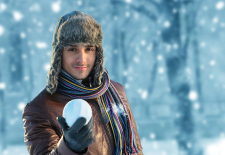 young fellow: Portrait of a smiling young man in an ear flap hat with a snowball in his hand