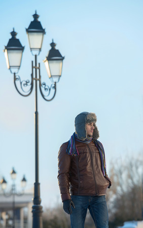 Winter walk - young man in an ear flap hat standing under the lamp post