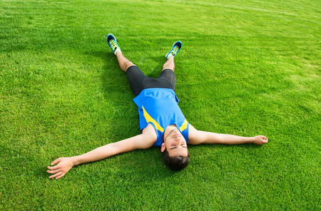 Tired athletic man lying on the grass