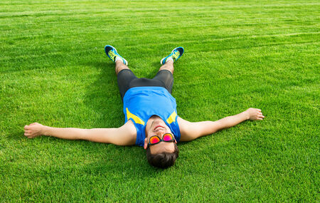 tired man: Tired athletic man lying on the grass