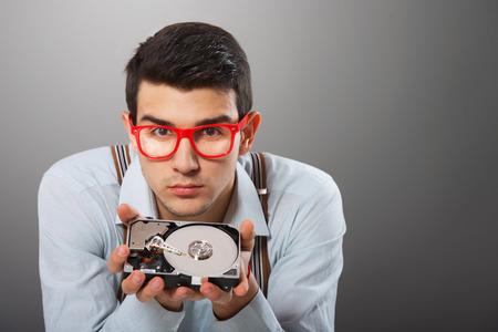 disco duro: Hombre en gafas rojo enmarcado con unidad de disco duro en sus manos mirando a la cámara