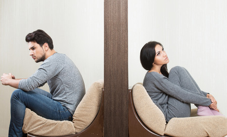 Conflict between man and woman sitting on either side of a wall Stockfoto