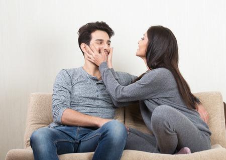 ソファの上に座って一緒に笑って幸せなカップル