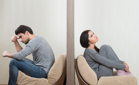 severance: Conflict between man and woman sitting on either side of a wall Stock Photo