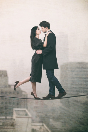 risky love: Couple in love standing on a rope over the city, crazy love concept