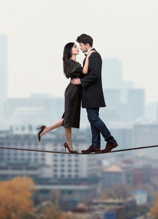 risky love: Coppia in amore in piedi su una corda sopra la citt�, il concetto di amore folle