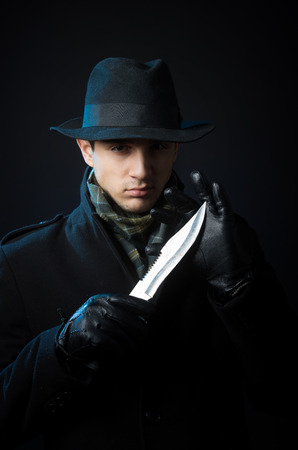 holding a knife: A man in black clothing holding a knife, studio shot, dark background Stock Photo