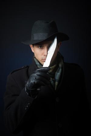 A man in black clothing holding a knife, studio shot, dark background photo