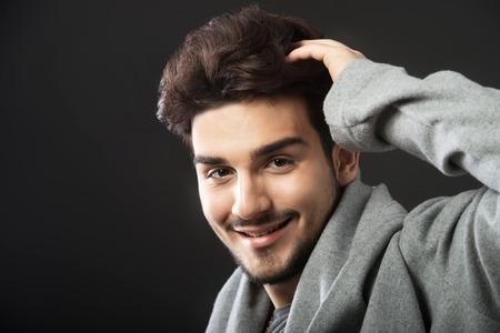 cowl: Man posing in gray cowl neck hoodie, studio portrait, dark background Stock Photo