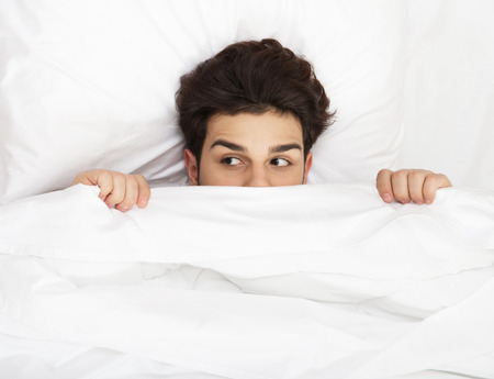 hide: Man hiding in bed under the sheets Stock Photo
