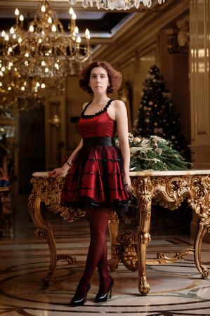 muebles antiguos: Retrato de cuerpo entero de una mujer en vestido de cóctel rojo en interior de lujo con decoración de Navidad Foto de archivo