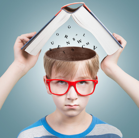 child education: Education concept - Boy looking at camera with a book and letters under his opened head Stock Photo