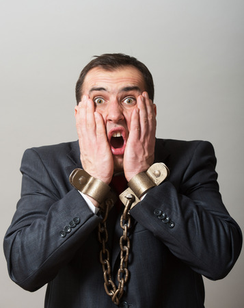 enchain: Shocked businessman with chained hands