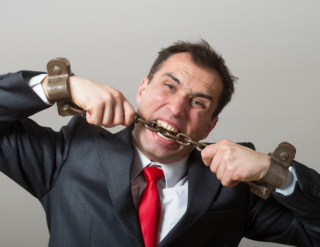 constrained: Desperate businessman biting through the shackles on his hands