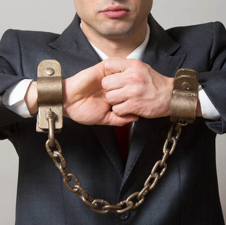 enchain: Linked male hands with the shackles Stock Photo