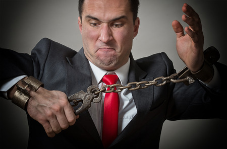 enchain: Angry businessman breaking the shackles on his hands Stock Photo