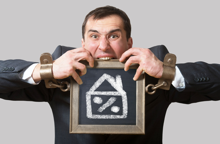 constrained: Chained man with a board mortgage concept