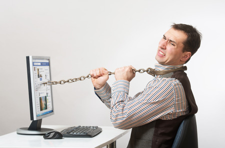 constrained: Man chained to his computer