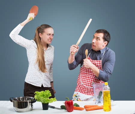 exaggeration: Working wife and househusband fighting in their kitchen Stock Photo