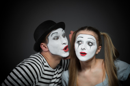 secret: Male mime sharing secret with surprised female mime