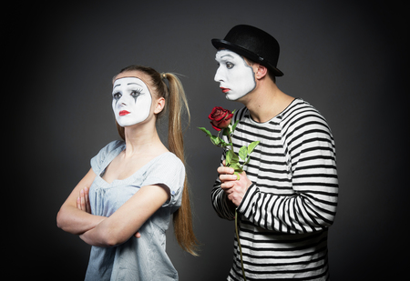 turn away: Male mime giving a flower to female mime