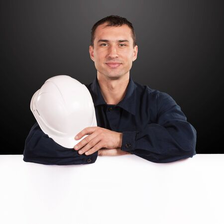 Portrait of a workman in dark blue coveralls with white hardhat in his hand