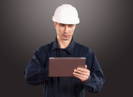 coveralls: Portrait of a workman in dark blue coveralls and white hardhat looking at tablet pc screen Stock Photo