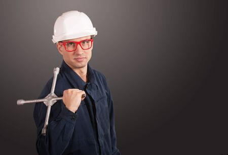 coveralls: Portrait of a workman in dark blue coveralls and white hardhat with a wheel wrench Stock Photo