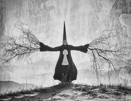 dunce cap: Fantasy portrait of a person wearing a long black cloak and a dunce hat with the branch hands Stock Photo
