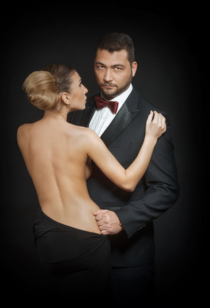 to undress: Portrait of a passionate couple on dark background