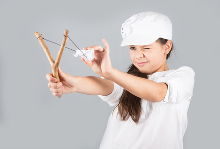 unruly: Preteen girl in white cap with a slingshot