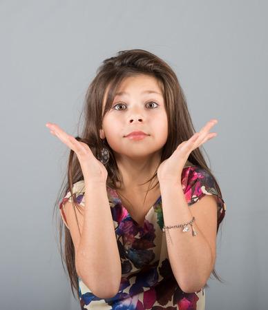 attitude girl: Portrait of an expressive preteen girl, studio shot, gray background Stock Photo