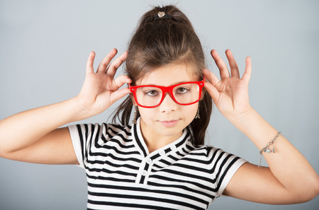 preteen model: Portrait of a cheerful preteen girl in red glasses, studio shot, gray background